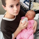 Alfie sosteniendo a Maisie, su hija que parece su hermana