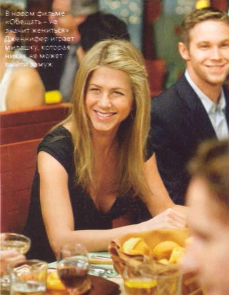 Jennifer Aniston sonriendo sentada, al lado de un hombre en foto de la revista Pink