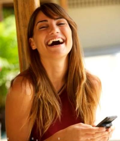 Mujer riendo con el movil en la mano