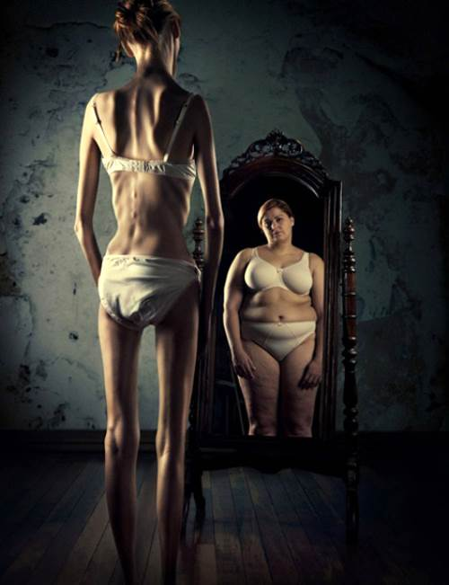 Mujer anorexica viendose gorda en un espejo