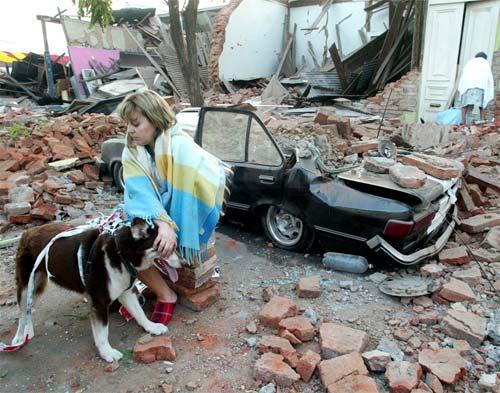Señora viendo viviendas destruidas con un perro en el terremoto de Chile