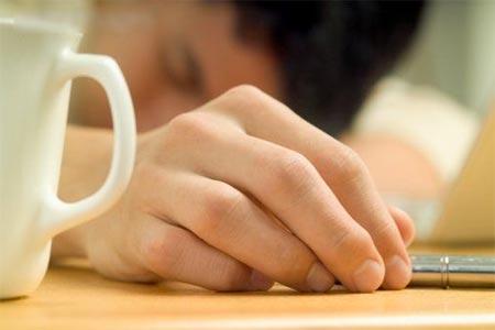 Hombre dormido con una taza de cafe
