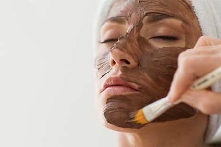 Mujer aplicandose una mascarilla de arcilla