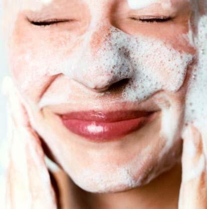 Mujer lavandose la cara con una sonrisa